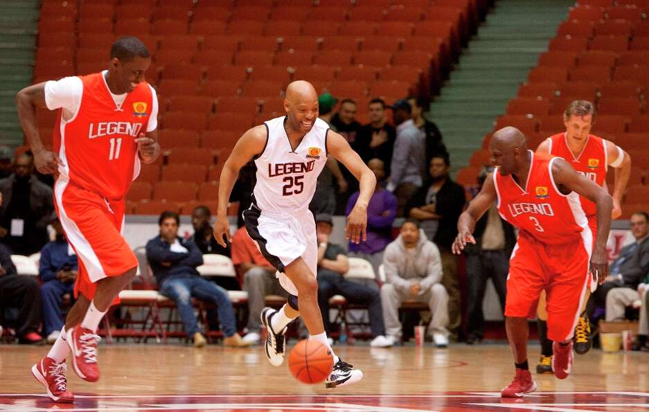 Sam Cassell, center, smiles after he stole the ball from  former Rocket Vernon Maxwell, left, during