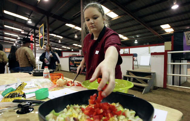 Mary Failla from East Bernard, Texas tosses red bell peppers into her skillet during the Food Challenge competition at the San Antonio Stock Show and Rodeo's junior contest on Saturday, Feb. 16, 2013. About 20 students from FFA and 4-H compete for scholarship money with their cooking skills as well as with their knowledge about nutrition, food prep and origin of ingredients. Students are given one of four categories to make a dish within a time limit without prior knowledge of the ingredients. Photo: Kin Man Hui, San Antonio Express-News / © 2012 San Antonio Express-News