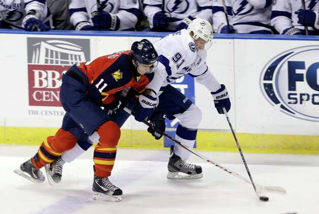 Florida Panthers' Jonathan Huberdeau (11) checks Tampa Bay Lightning's Steven Stamkos (91) in the second period of an NHL hockey game in Sunrise, Fla., Saturday, Feb. 16, 2013. (AP Photo/Alan Diaz) Photo: Alan Diaz