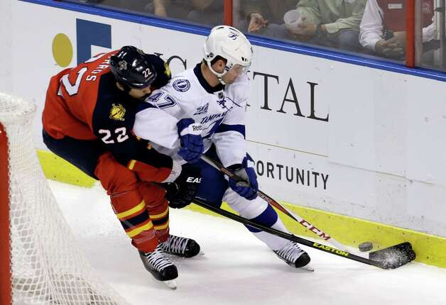 Florida Panthers' George Parros (22) checks Tampa Bay Lightning's Marc-Andre Bergeron (47) in the second period of an NHL hockey game in Sunrise, Fla., Saturday, Feb. 16, 2013. (AP Photo/Alan Diaz) Photo: Alan Diaz