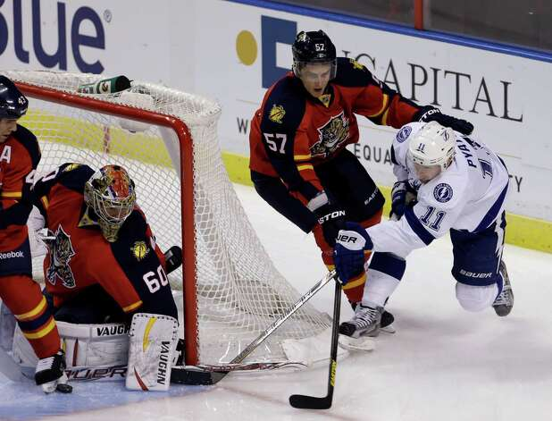 Florida Panthers goalie Jose Theodore (60) blocks a shot by Tampa Bay Lightning's Tom Pyatt (11) in the first period of an NHL hockey game as Marcel Goc (57) defends  in Sunrise, Fla., Saturday, Feb. 16, 2013. (AP Photo/Alan Diaz) Photo: Alan Diaz