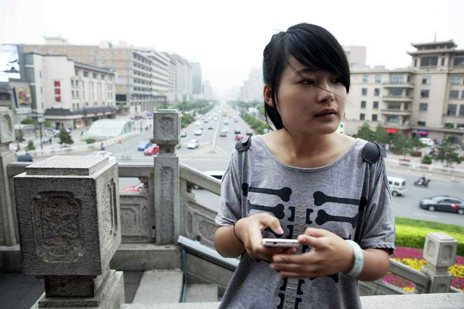 Wu Caoying, in Xi'an, China, reluctantly continues her college education, which costs more than half of her parents' combined annual income. Photo: Ryan Pyle / New York Times