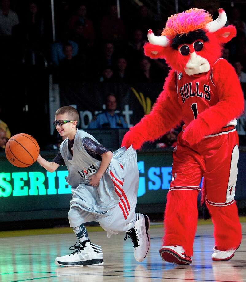 Chicago Bulls mascot, Benny, holds on Brandon Srebnik, 7, as he makes his way to the basket wearing NBA-player-sized clothes before All-Star practice at the George R. Brown Convention Center, Saturday, Feb. 16, 2013, in Houston. Photo: Cody Duty / © 2013 Houston Chronicle