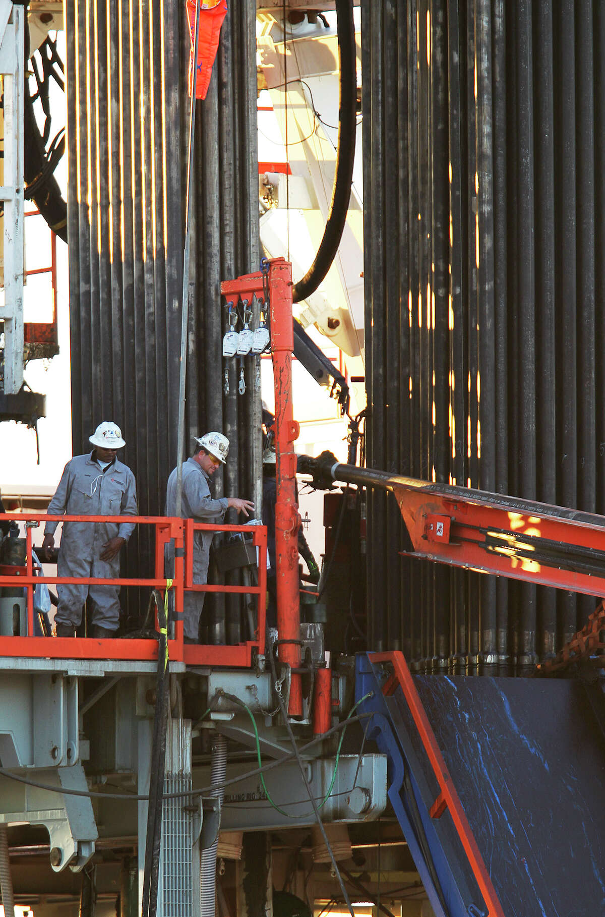 Workers are seen on the drill floor of Patterson-UTI Energy Rig 248 on FM 99 in Live Oak County near Whisett, Texas, Wednesday, Feb. 13, 2013.