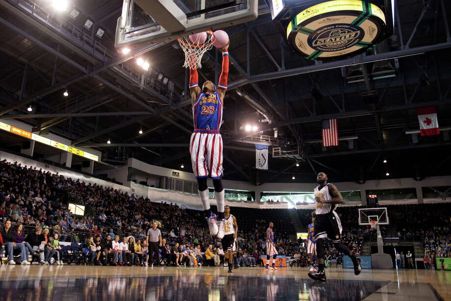 Harlem Globetrotter Hacksaw Hall dunks two balls during a performance of the Harlem Globetrotters on Saturday, February 16, 2013 at the Showare Center in Kent. The Globetrotters also have performances scheduled in Everett on Sunday (Feb. 17th) and Seattle on Monday (Feb. 18th) during their tour of the area. Photo: JOSHUA TRUJILLO, SEATTLEPI.COM / SEATTLEPI.COM