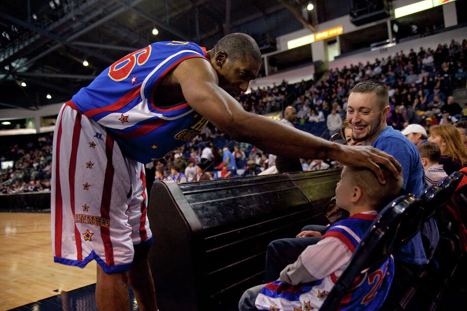 Harlem Globetrotter Hi-Lite Bruton greets fan Hunter Hamre, 4, with his dad Shane Hamre during a performance of the Harlem Globetrotters on Saturday, February 16, 2013 at the Showare Center in Kent. The Globetrotters also have performances scheduled in Everett on Sunday (Feb. 17th) and Seattle on Monday (Feb. 18th) during their tour of the area. Photo: JOSHUA TRUJILLO, SEATTLEPI.COM / SEATTLEPI.COM