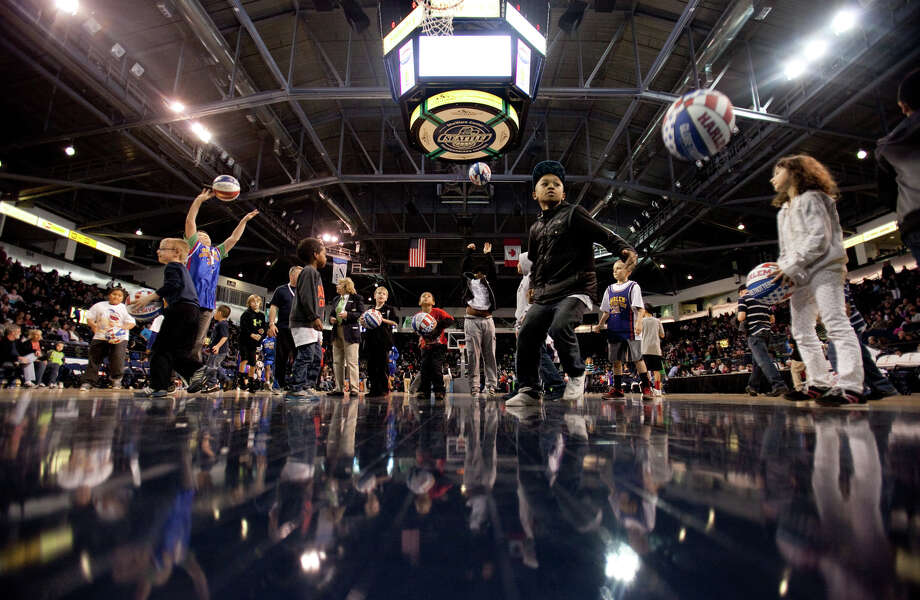Kids shoot baskets during halftime of a performance of the Harlem Globetrotters on Saturday, February 16, 2013 at the Showare Center in Kent. The Globetrotters also have performances scheduled in Everett on Sunday (Feb. 17th) and Seattle on Monday (Feb. 18th) during their tour of the area. Photo: JOSHUA TRUJILLO, SEATTLEPI.COM / SEATTLEPI.COM
