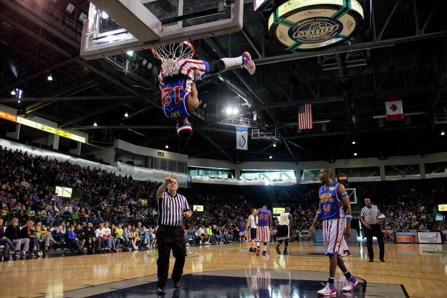 Harlem Globetrotter Ant Atkinson hangs from the rim during a performance of the Harlem Globetrotters on Saturday, February 16, 2013 at the Showare Center in Kent. The Globetrotters also have performances scheduled in Everett on Sunday (Feb. 17th) and Seattle on Monday (Feb. 18th) during their tour of the area. Photo: JOSHUA TRUJILLO, SEATTLEPI.COM / SEATTLEPI.COM