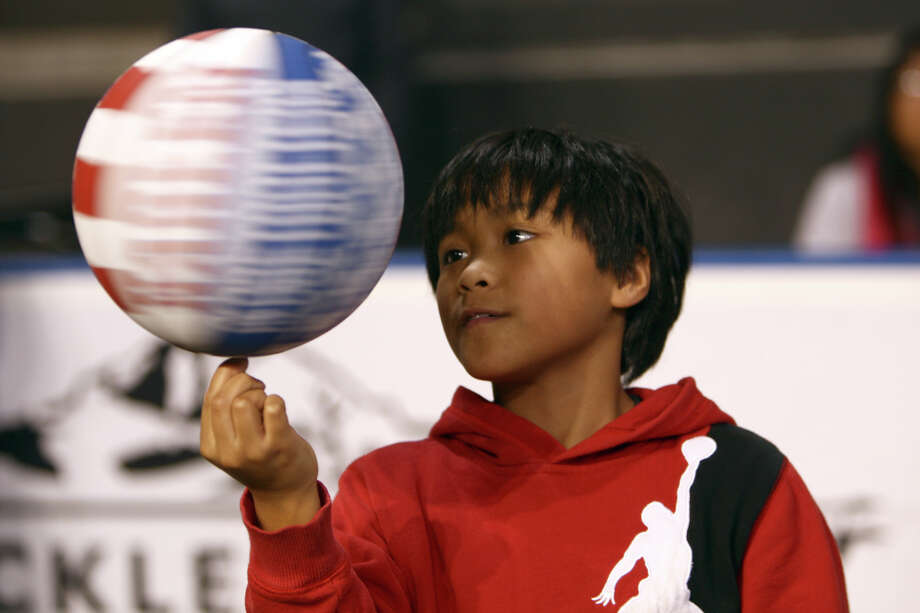 Bradley Baltazar, 10, spins a ball during halftime of a performance of the Harlem Globetrotters on Saturday, February 16, 2013 at the Showare Center in Kent. The Globetrotters also have performances scheduled in Everett on Sunday (Feb. 17th) and Seattle on Monday (Feb. 18th) during their tour of the area. Photo: JOSHUA TRUJILLO, SEATTLEPI.COM / SEATTLEPI.COM
