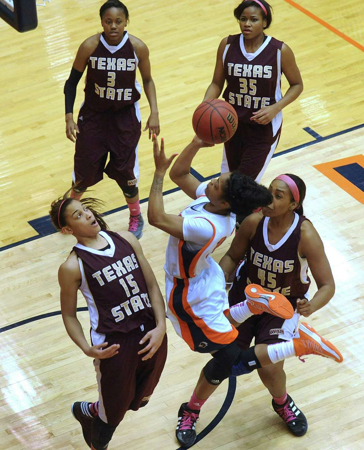 Senior guard Simone Young of UTSA shoots a layup as Jasmine Baugus (15), Diamond Ford (3), Erin Peoples (35) and Ashley Ezeh of Texas State defend during women's college basketball action at UTSA on Saturday, Feb. 16, 2013.