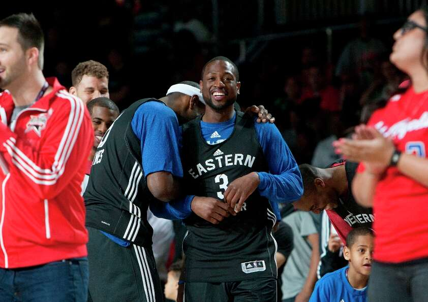 Miami Heat's Lebron James laughs on teammate Dwayne Wade's shoulder during All-Star practice at the