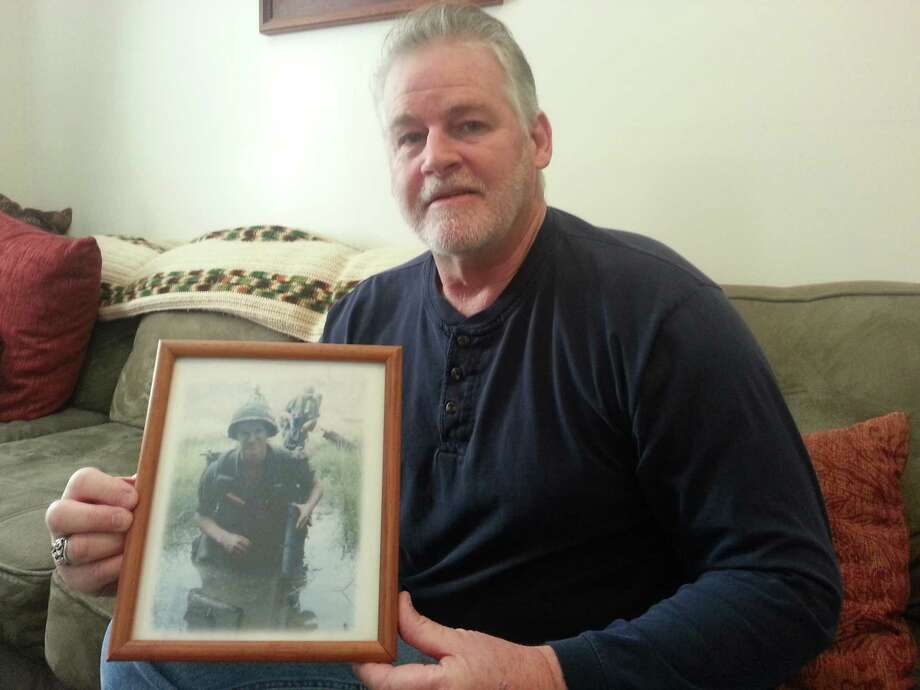 Michael Guenette of Waterford holds a portrait of his brother, Peter Guenette of Lansingburgh, who died May 18, 1968, in Vietnam, where he jumped on an enemy grenade to save the lives of soldiers he was with. Peter Guenette posthumously received the Medal of Honor, the nation's highest military honor (Dennis Yusko).