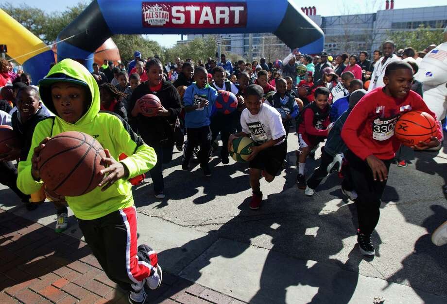 Contestants participate in a dribble race during the All-Star FIT, Walk & Dribble, at Discovery Green, Saturday, Feb. 16, 2013, in Houston. The event featured former NBA stars along with a 5k run, a 1k walk and a dribble for kids. Photo: Cody Duty, Houston Chronicle / © 2013 Houston Chronicle