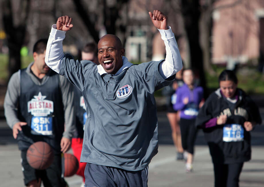 Former NBA player T.J. Ford celebrates while crossing the finish line of a 5k race during the All-Star FIT, Walk & Dribble, at Discovery Green, Saturday, Feb. 16, 2013, in Houston. Photo: Cody Duty, Houston Chronicle / © 2013 Houston Chronicle