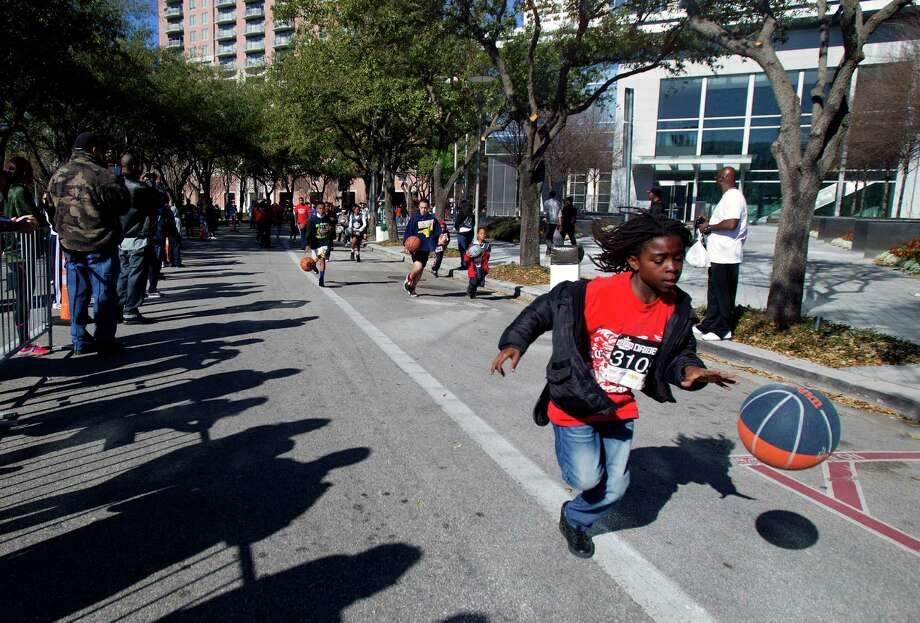 Contestants participate in a dribble race during the All-Star FIT, Walk & Dribble, at Discovery Green, Saturday, Feb. 16, 2013, in Houston. Photo: Cody Duty, Houston Chronicle / © 2013 Houston Chronicle