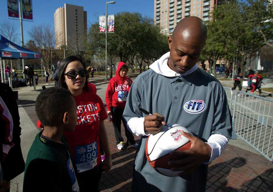 Former NBA player T.J. Ford signs an autograph for fans during the All-Star FIT, Walk & Dribble, at Discovery Green, Saturday, Feb. 16, 2013, in Houston. Photo: Cody Duty, Houston Chronicle / © 2013 Houston Chronicle