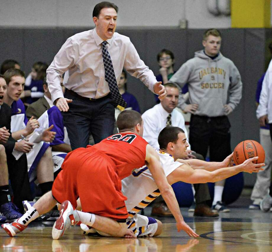 UAlbany head coach Will Brown calls out to player Jacob Iati as he wrestles the ball from Hartford's #00 Wes Cole during Saturday's game at SEFCU Arena in Albany Feb. 16, 2013.  (John Carl D'Annibale / Times Union) Photo: John Carl D'Annibale / 00021154A