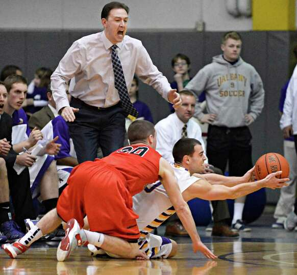 UAlbany head coach Will Brown calls out to player Jacob Iati as he wrestles the ball from Hartford's