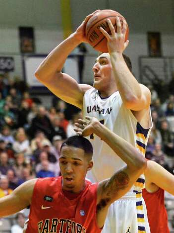UAlbany's #14 Sam Rowley, top, gets over Hartford's #15 Yolonzo Moore II during Saturday's game at SEFCU Arena in Albany Feb. 16, 2013.  (John Carl D'Annibale / Times Union) Photo: John Carl D'Annibale / 00021154A