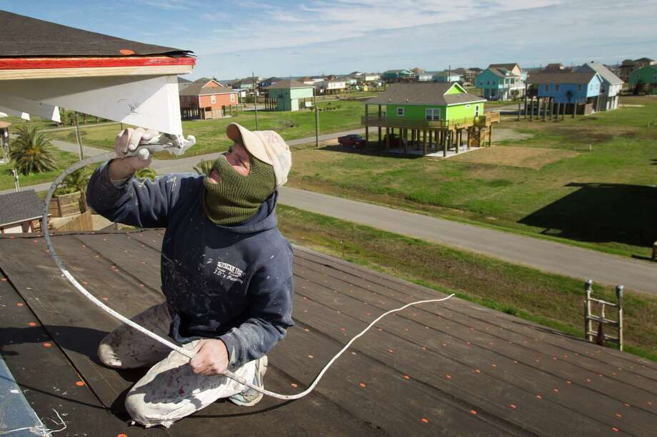 Jimmy Wiggins of Acadian Builders works last week on a new home under construction as newly built homes can be seen in the background in Crystal Beach, as the Bolivar Peninsula is experiencing a comeback Photo: Brett Coomer, Staff / © 2013 Houston Chronicle