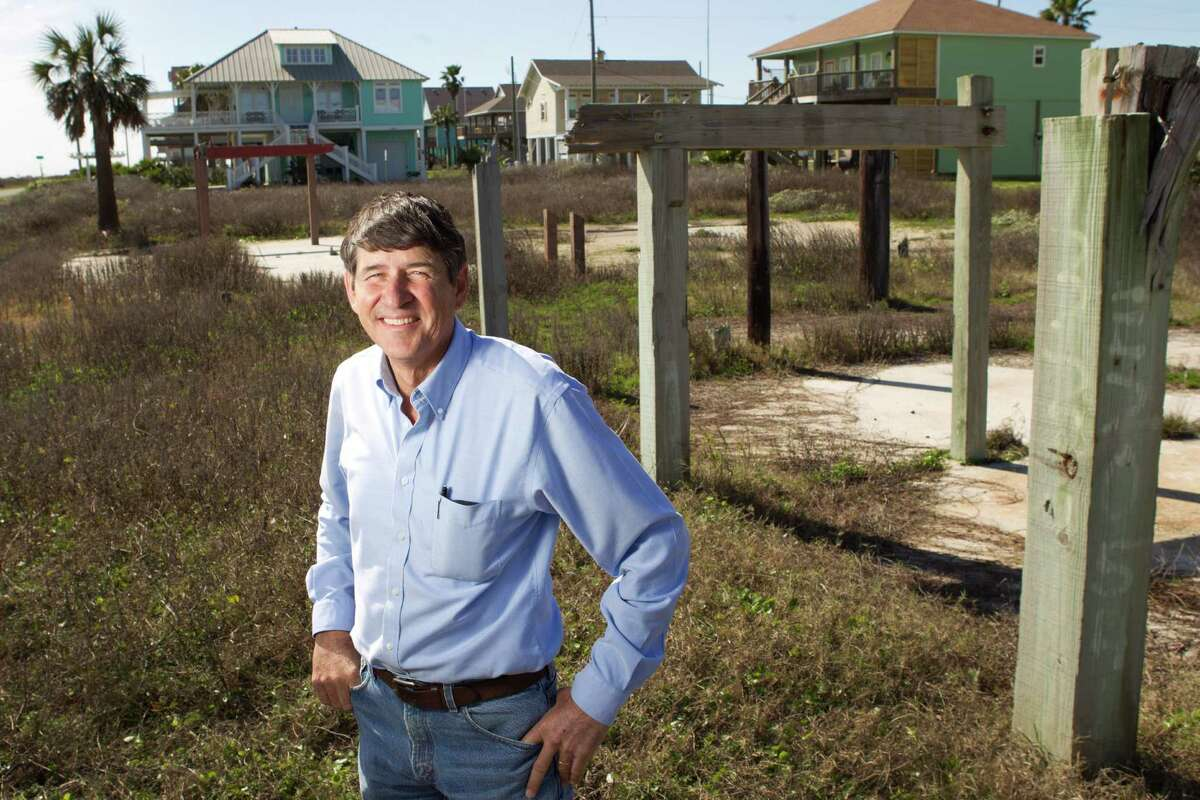 Sid Bouse, a member of the Bolivar Blue Ribbon recovery committee, stands among pilings from a destroyed home next to newly-built homes Wednesday, Feb. 13, 2013, in Crystal Beach, Texas.