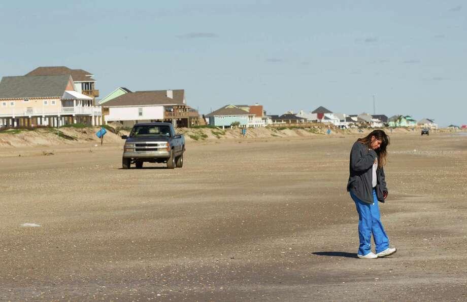 Christal Mears walks along the beach near a line of recently-built homes on Wednesday, Feb. 13, 2013, in Crystal Beach, Texas. Photo: Brett Coomer, Houston Chronicle / © 2013 Houston Chronicle