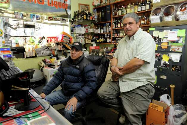 Calixto Jimenez, left, and his brother Juan Jimenez, of Discount Liquors in Danbury, talk about the disappearance of the Brazilian trade in Danbury, Conn. Wed. Feb. 13, 2013. Photo: Carol Kaliff / The News-Times