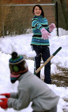 Akiko Montanaro, 12, throws a snowball at her little brother SeungNam, 8, as they play in front of their home on Lafayette Street in Bridgeport, Conn. on Saturday February 16, 2013. Photo: Christian Abraham / Connecticut Post