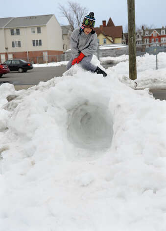 SeungNam Montanaro, 8, plays atop a snow fort he built in front of his home on Lafayette Street in Bridgeport, Conn. on Saturday February 16, 2013. Photo: Christian Abraham / Connecticut Post