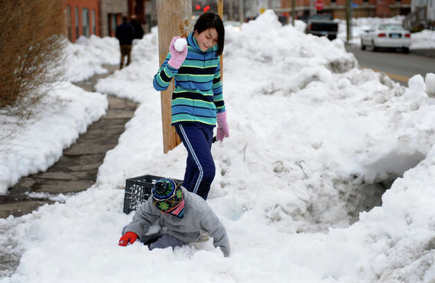Akiko Montanaro, 12, gets ready to throw a snowball at her little brother SeungNam, 8, as they play in front of their home on Lafayette Street in Bridgeport, Conn. on Saturday February 16, 2013. Photo: Christian Abraham / Connecticut Post