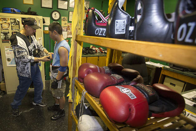 Santo (Sam) Randazzo (left) helps Victor Maza, 16, with his boxing gloves recently at the Randazzo Brothers Boxing Gym on the Northeast Side. The facility opened in 2008. Photo: Michael Miller / For The Express-News