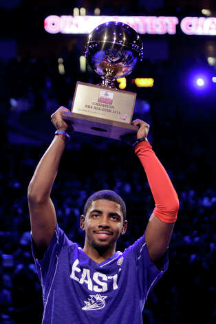 Kyrie Irving of the Cleveland Cavaliers hoists the trophy after winning the NBA All-Star Three-Point Contest at the Toyota Center on All-Star Saturday Night, Saturday, Feb. 16, 2013, in Houston. Photo: Melissa Phillip, Houston Chronicle / © 2013  Houston Chronicle