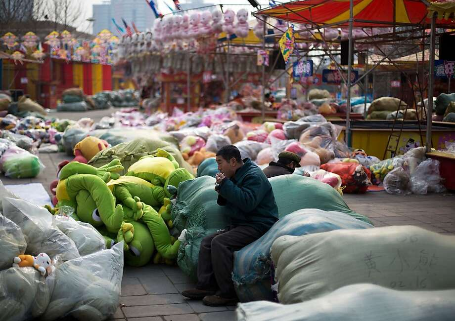 A migrant worker takes lunch break on the bags of soft toys dismantled from the stores after the end of the Chinese Lunar New Year temple fair at a park in Beijing Saturday, Feb. 16, 2013. Millions of people start to rush back to workplaces all over China when a week long Lunar New Year holiday comes to an end. Photo: Andy Wong, Associated Press