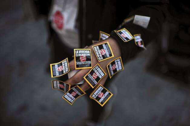 A hand of demonstrator displays stickers against evictions, in  Pamplona, northern Spain on Saturday, Feb. 16, 2013. Demonstrations are being held across Spain to protest harsh repossession laws that have led to hundreds of thousands of evictions during the country's deep recession. More than 350,000 Spaniards have received eviction orders since 2008 because they were unable to make mortgage payments. Photo: Alvaro Barrientos, Associated Press