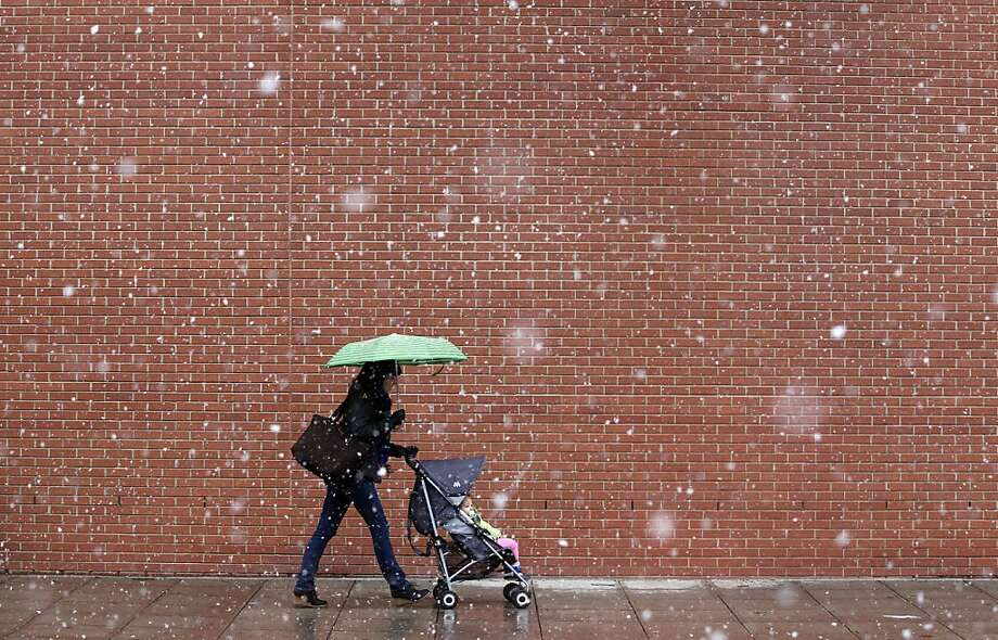 People walk as snow falls in downtown Raleigh, North Carolina, Saturday, February 16, 2013. Photo: Ethan Hyman, McClatchy-Tribune News Service