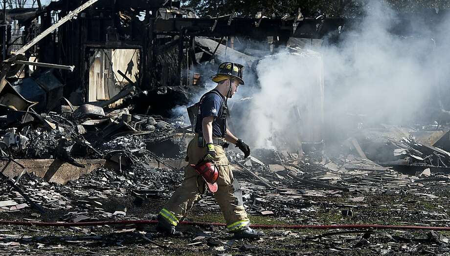 A Bryan firefighter walks across the smoking rubble of a Knights of Columbus Hall in Bryan, Texas, Saturday, Feb. 16, 2013.  Two Texas fire lieutenants have died of burns after battling a lodge hall fire, and two are hospitalized, a city official said Saturday. Photo: Stuart Villanueva, Associated Press