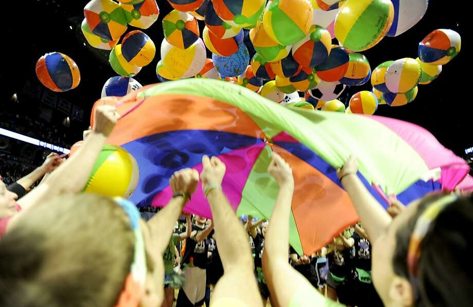 An operations committee launches beach balls into the air with a parachute during the Penn State IFC/Panhellenic Dance Marathon at the Bryce Events Center in University Park, Pennsylvania, on Saturday, February 16, 2013. Dancers started the 46-hour fundraiser on Friday. The event, known as Thon, raises money to help families that are battling pediatric cancer. Last year's event raised $10 million.  Photo: Abby Drey, McClatchy-Tribune News Service