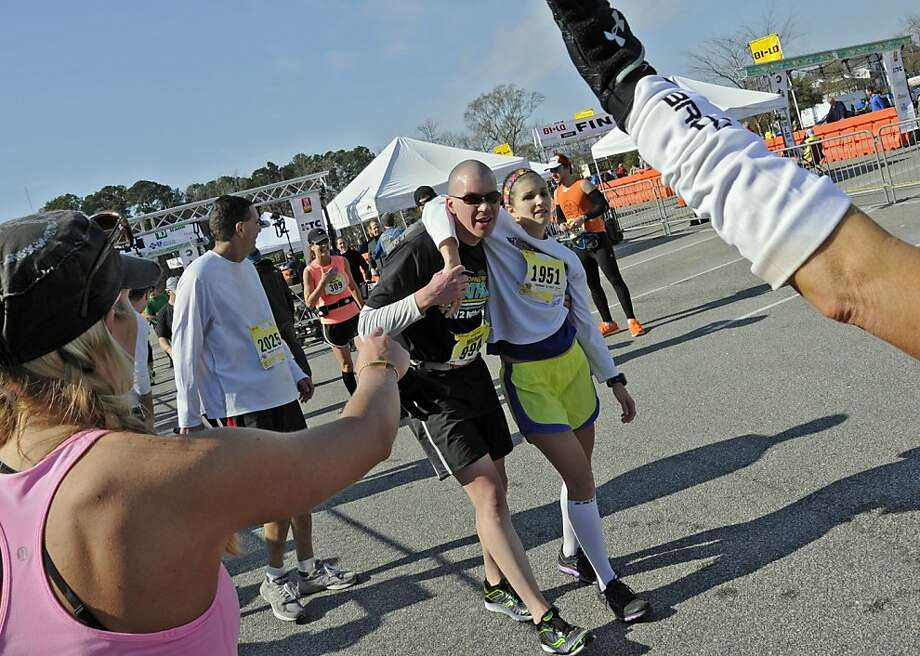 Michael Marquis gives a hand to Morgan Hearns after she crossed the finish line of the annual Bi Lo Myrtle Beach Marathon, Saturday, Feb. 16, 2013, in Myrtle Beach, S.C. Both are from Huntersville, N.C.  Photo: Charles Slate, Associated Press