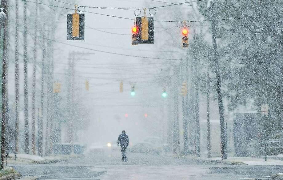 Snow flurries create a haze, Saturday, Feb. 16, 2013, along Washington Street as winter weather sets in over Kinston, N.C.  Photo: Janet S. Carter, Associated Press
