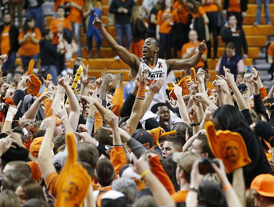 Oklahoma State guard Markel Brown (22) celebrates with fans following a 84-79 victory over Oklahoma in an NCAA college basketball game in Stillwater, Okla., Saturday, Feb. 16, 2013. Photo: Sue Ogrocki, Associated Press