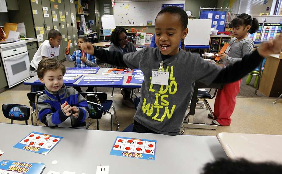 Christopher Larry, Jr., right, reacts to winning a letter bingo game as Joel McCain looks on in their kindergarten classroom at Campbell Hill Elementary in Renton, Wash. Washington is one of two states (the other being Pennsylvania) that doesn't require kids to start their educations until age 8. A bill in the House would lower the mandatory age to 6, but would exempt home-schoolers, who wouldn't fall under the state's instructional supervision until age 8.  Photo: Elaine Thompson, Associated Press