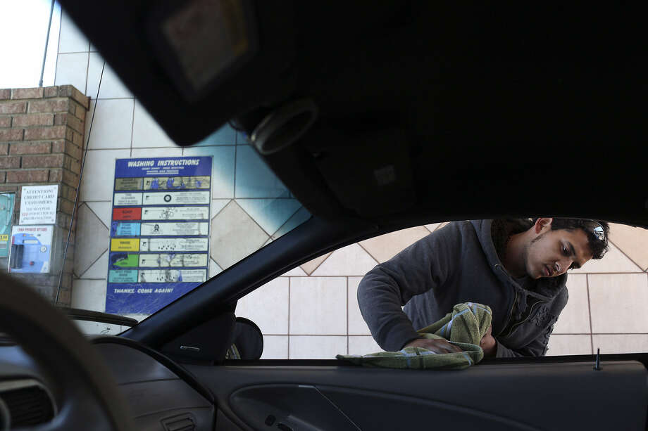 Thomas Clarke wipes down his car after washing it at the NDS Self Service Car Wash on Bandera Road. Under the new rules, people will be able to wash their cars at home once per week on Saturday or Sunday. Photo: Lisa Krantz / San Antonio Express-News