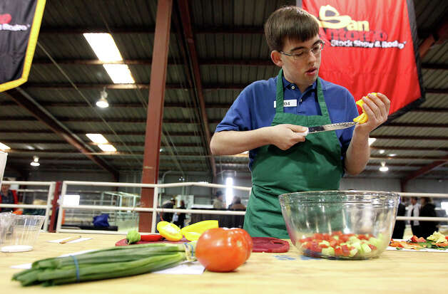 Logan Moore from Boyd, Texas cuts into a bell pepper during the Food Challenge competition at the San Antonio Stock Show and Rodeo's junior contest on Saturday, Feb. 16, 2013. About 20 students from FFA and 4-H compete for scholarship money with their cooking skills as well as with their knowledge about nutrition, food prep and origin of ingredients. Students are given one of four categories to make a dish within a time limit without prior knowledge of the ingredients. Photo: Kin Man Hui, San Antonio Express-News / © 2012 San Antonio Express-News