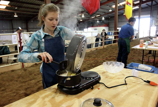 Claire Weber of La Vernia mixes her ingredients together to make a potato soup during the Food Challenge competition at the San Antonio Stock Show and Rodeo's junior contest on Saturday, Feb. 16, 2013. About 20 students from FFA and 4-H compete for scholarship money with their cooking skills as well as with their knowledge about nutrition, food prep and origin of ingredients. Students are given one of four categories to make a dish within a time limit without prior knowledge of the ingredients. Photo: Kin Man Hui, San Antonio Express-News / © 2012 San Antonio Express-News