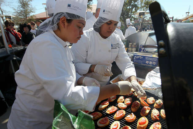 Culinary students Bridget Estrada (left) and Priscilla Aguilar from St. Philips College prepare crostini to be paired with a wine at the H-E-B Wine Garden at the San Antonio Stock Show and Rodeo on Saturday, Feb. 16, 2013. Crostini consists of tomato, basil, Romano cheese on toasted bread. Photo: Kin Man Hui, San Antonio Express-News / © 2012 San Antonio Express-News