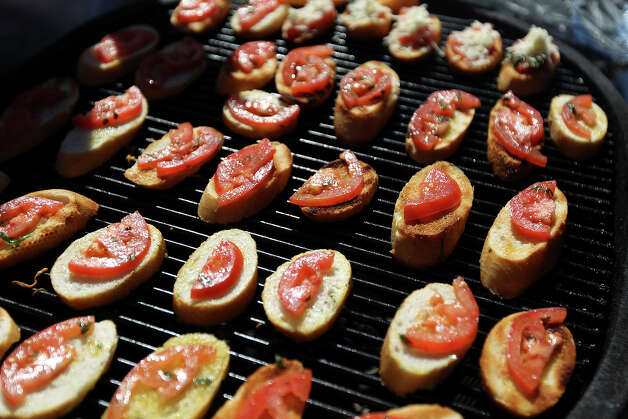 Crostini are toasted on a outdoor grill by culinary students from St. Philips College at the H-E-B Wine Garden at the San Antonio Stock Show and Rodeo on Saturday, Feb. 16, 2013. Photo: Kin Man Hui, San Antonio Express-News / © 2012 San Antonio Express-News