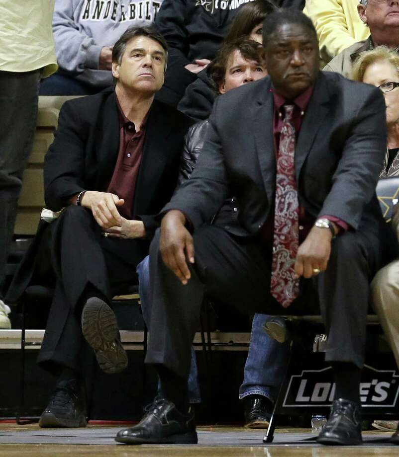 Texas Gov. Rick Perry, left, watches Texas A&M play Vanderbilt in an NCAA college basketball game on Saturday, Feb. 16, 2013, in Nashville, Tenn. At right is Barry Davis, director of player development for A&M. (AP Photo/Mark Humphrey) Photo: Mark Humphrey, Associated Press / AP