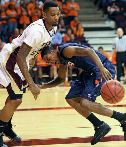 Hyjii Thomas crashes into Bobcat defender Joel Wright as Texas State hosts UTSA in men's basketball at Strahan Coliseum  on February 16, 2013. Photo: Tom Reel, San Antonio Express-News