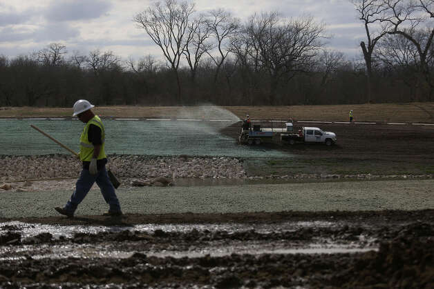 A mulchlike material is sprayed over freshly seeded soil as construction and landscaping continues along the Mission Reach of the San Antonio River Photo: Lisa Krantz / San Antonio Express-News