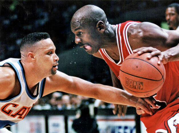 In this 1994 file photo, Chicago Bulls great Michael Jordan, right, goes in for a shot against Cleveland Cavaliers' Chris Mills during an NBA basketball game at the Coliseum in Richfield, Ohio. The Shot Jordan buried to eliminate the Cavaliers from the playoffs in 1989, only added to the legend of the curse on Cleveland's sports teams. Photo: Mark Duncan, AP / AP